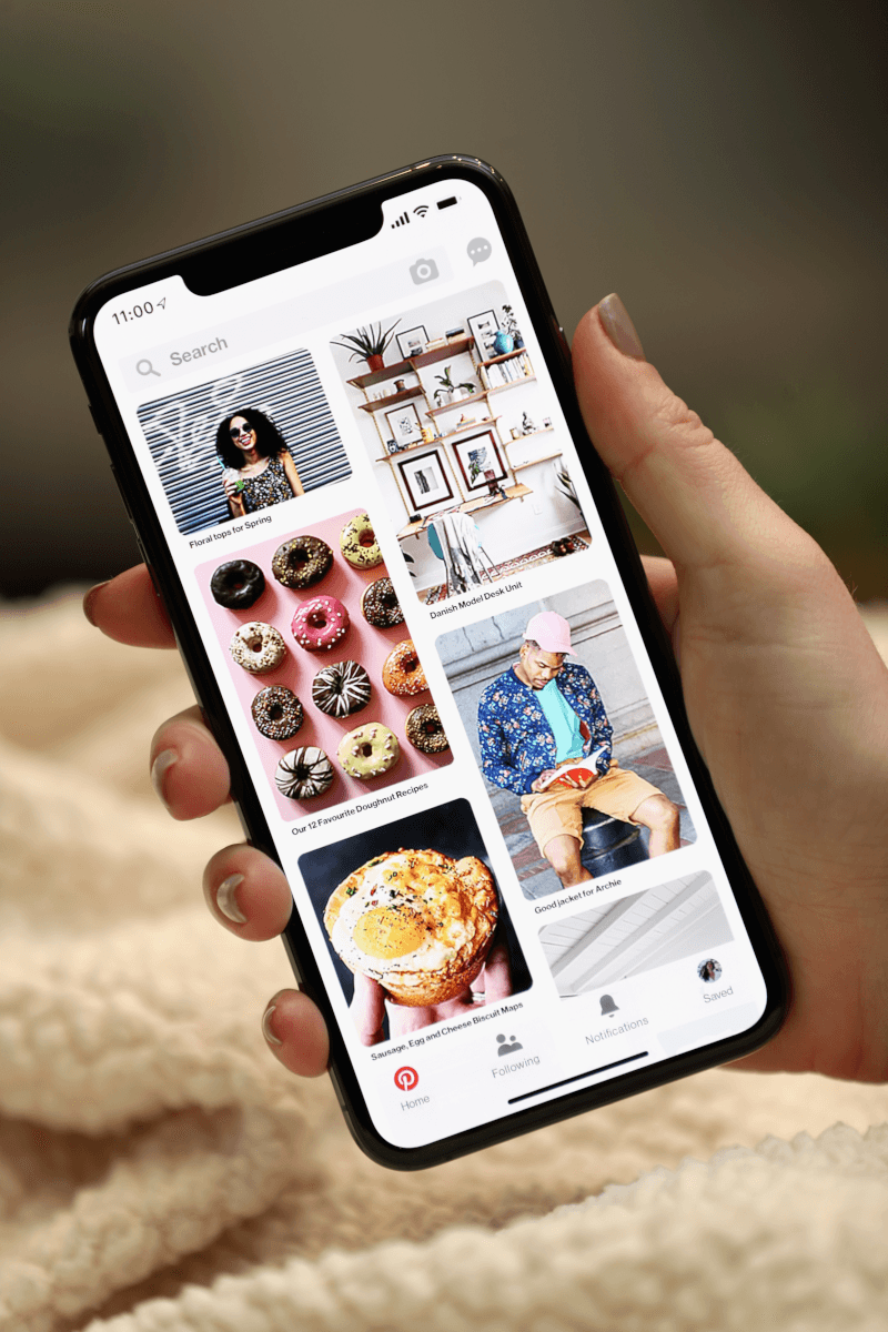A hand holding an iPhone XR over a white blanket. The screen is displaying the Pinterest homepage.