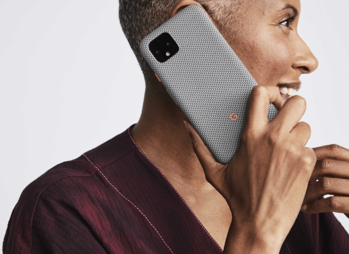 A woman with a tight, grey haircut, holds a grey Pixel 4 to her ear. She is wearing a burgundy top and standing in front of a grey background.