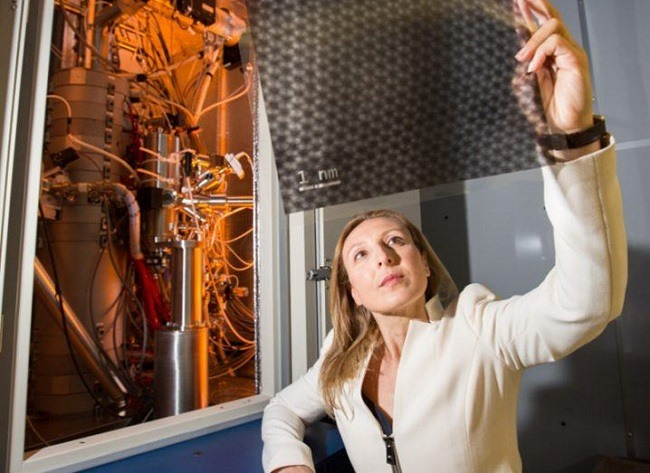Valeria Nicolosi in a white blazer holding a sheet of nanomaterial up to the ligt in her lab.