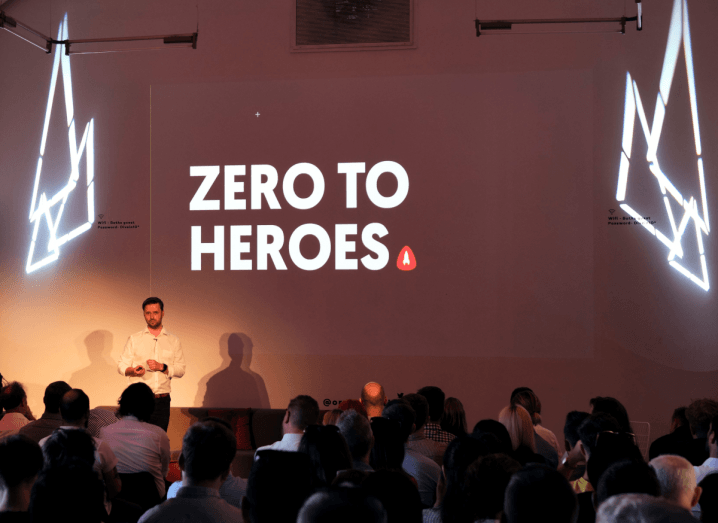 """A man standing in front of a projection on a wall that says """"Zero to Heroes"""", while addressing an audience in front of him in a dark room."""