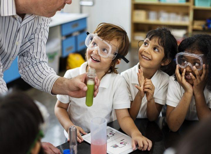 Kids wearing protective glasses looking happy in science class while looking at their teacher holding a test tube with green liquid in it.