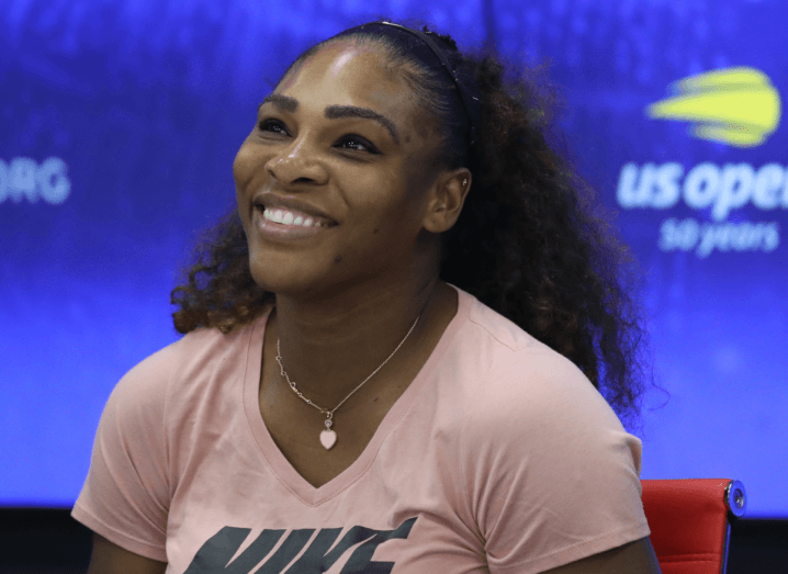 "Serena Williams smiles in front of a blue background, wearing a pink T-shirt with ""Nike"" written on the front of it. She has long, black curly hair that is pulled back by a hairband."