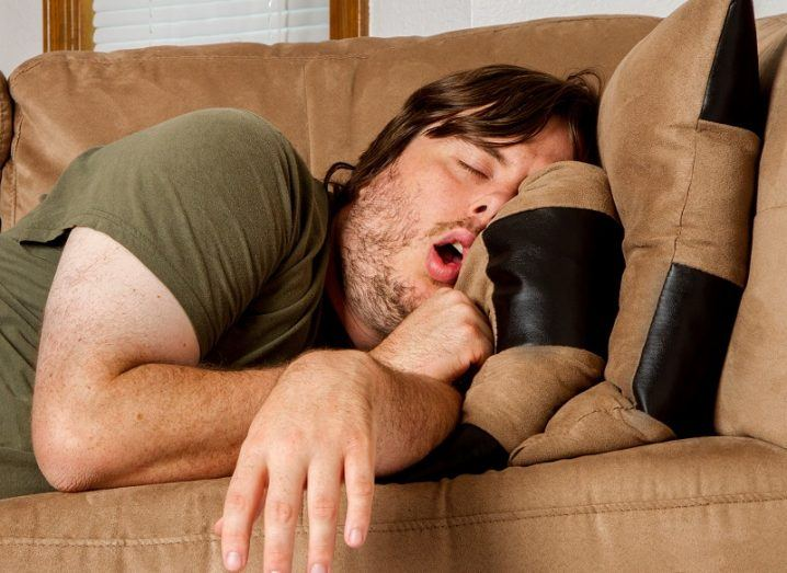 Man in green T-shirt asleep with mouth open on a brown couch.
