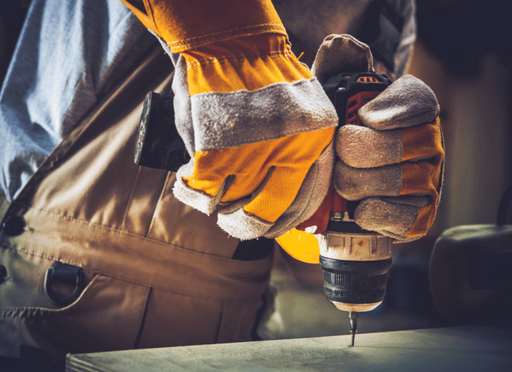 A worker wearing yellow and grey gloves, with brown overalls, uses a screwdriver to screw a hole into a flat surface below them.