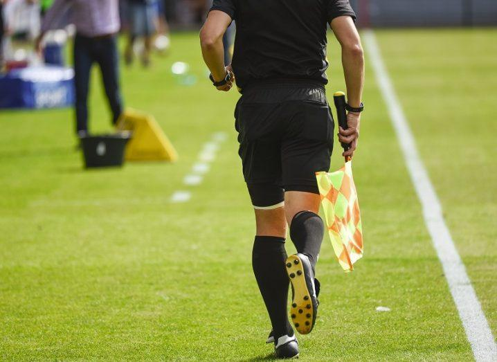 Sideline referee holding a flag, running along the side of a football pitch.