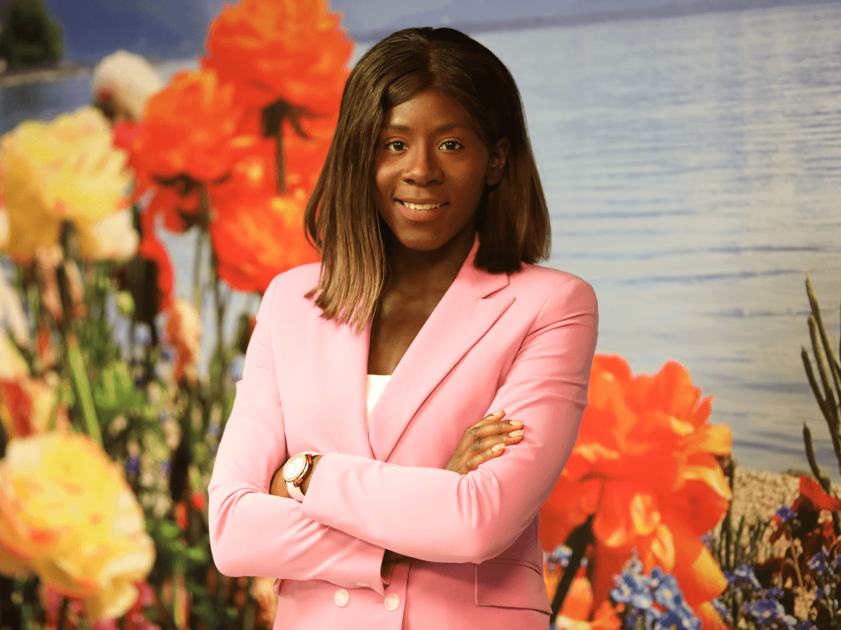 A young woman in a pink suit stands with her arms crossed in front of a wall covered in flowers. She has brown, shoulder length hair.