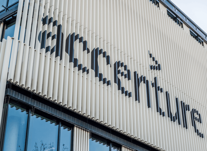 The Accenture logo in black on a white panelled background, on the exterior of a building.