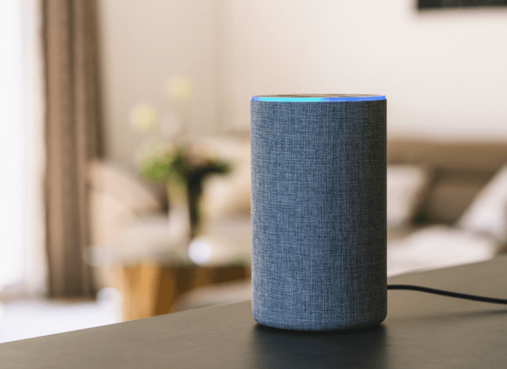 An Amazon Echo smart speaker on a surface in a living room.