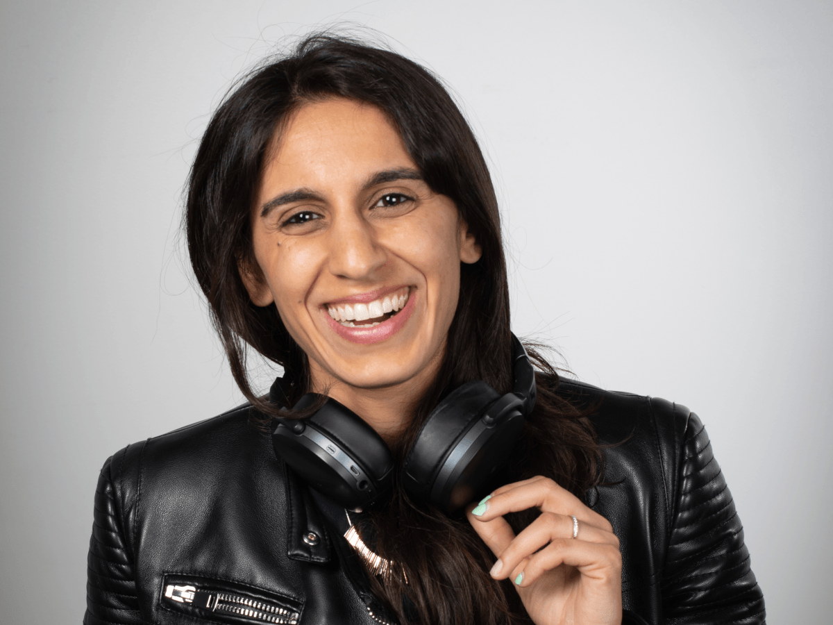 A woman with brown hair, wearing headphones over her shoulders and a leather jacket smiles into the camera in front of a grey background.