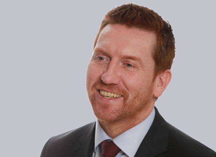 A close-up of a man with red hair, wearing a suit.