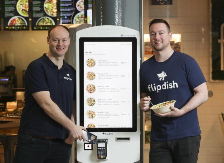 Two men in blue 'Flipdish' T-shirts stand beside a self-service ordering kiosk, which is displaying different salad options for purchase.