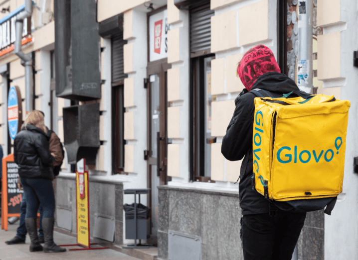 A Glovo courier walking down a street in Ukraine wearing a yellow Glovo backpack.