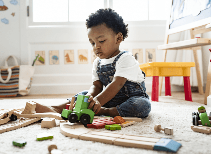 A young child wearing dungarees and a white T-shirt plays with a wooden, green toy train in a play room.