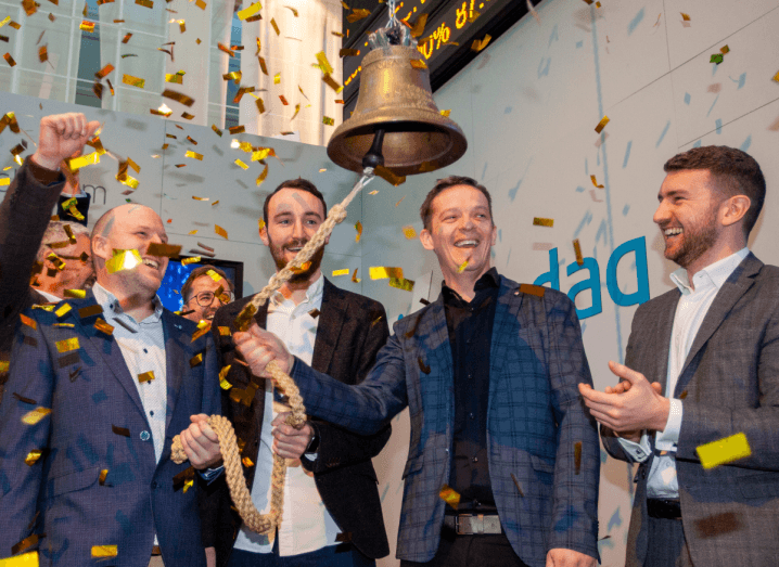 A group of four men ringing a bell in a white room, where confetti is dropping from the ceiling.