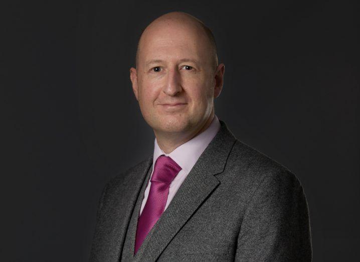 View of bald man in business attire, grey blazer, white shirt, purple tie, standing against dark background.