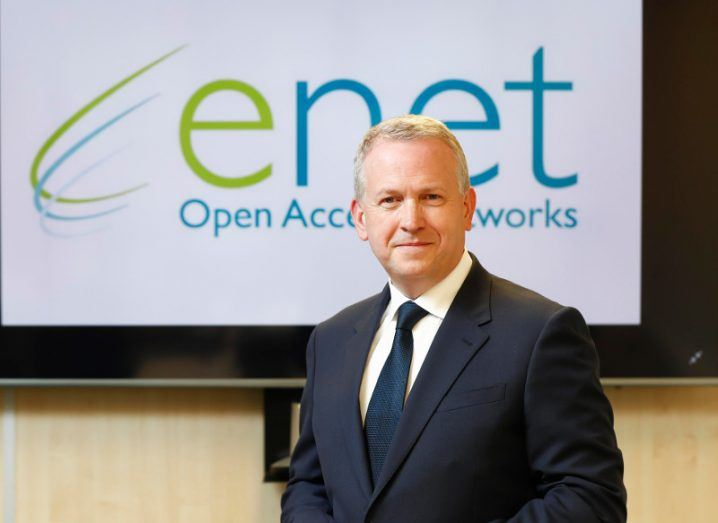 A man in a dark suit stands in front of a screen that says 'enet'.