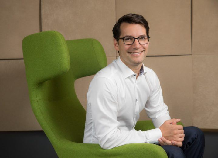 A man with dark hair and glasses, wearing a white shirt, sits in a bright green chair.