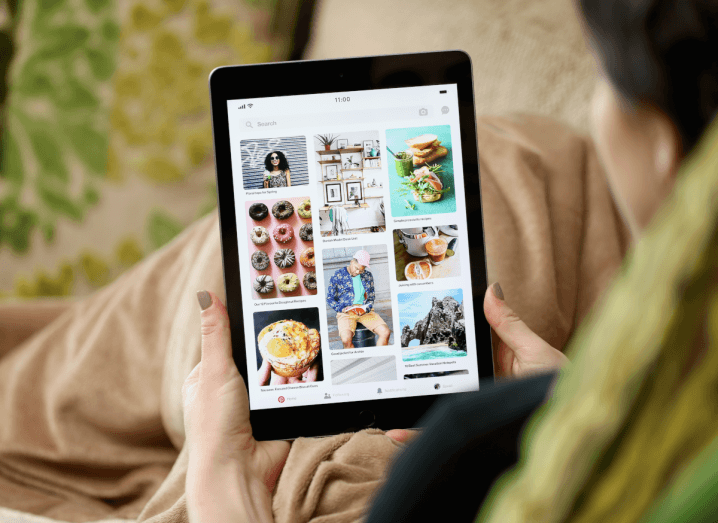 A woman browsing the Pinterest feed on an iPad, while sitting under a brown blanket.