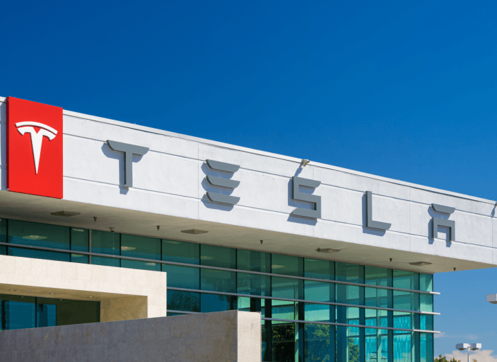 The exterior of a Tesla retail store under a blue sky.