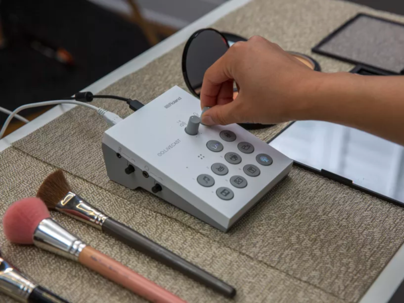 A livestreamer touching the Roland device as it sits on a desk beside makeup brushes.