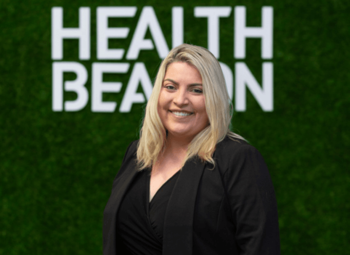 A woman standing in front of a green background with the HealthBeacon logo, wearing a black suit.