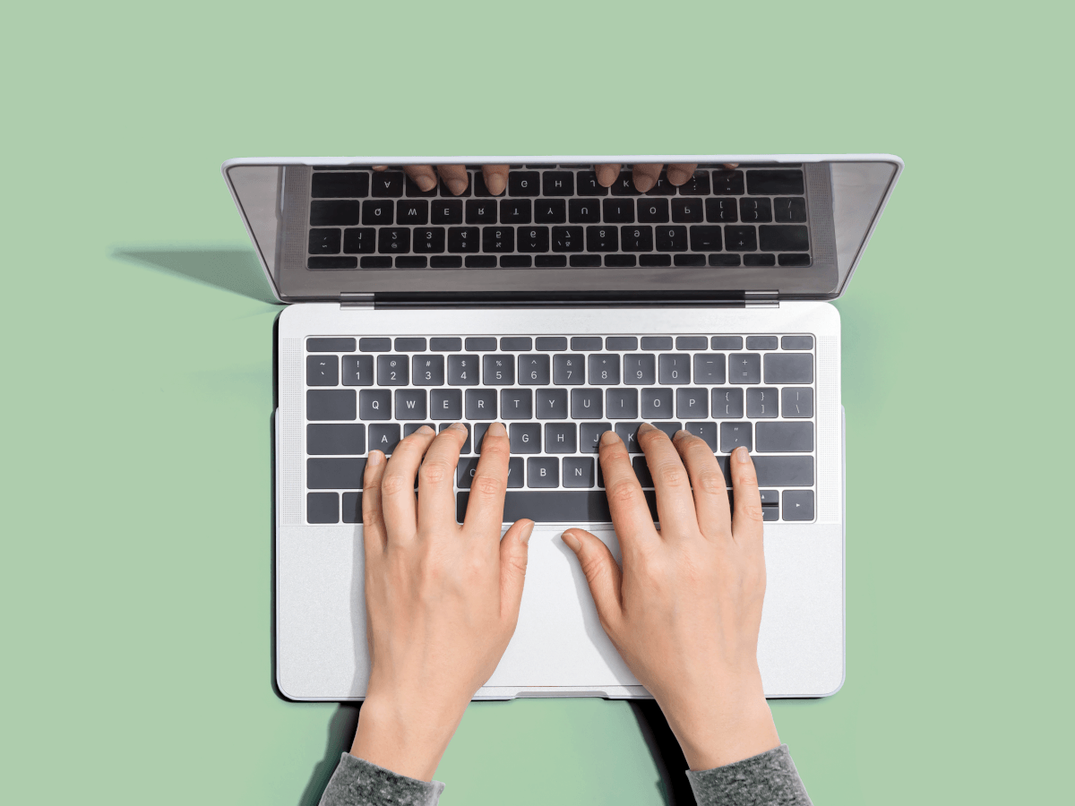 Pale green background with hands typing on a laptop symbolising the future of work.