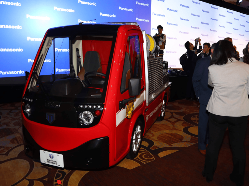 A small, one-seater red firetruck in a conference room.