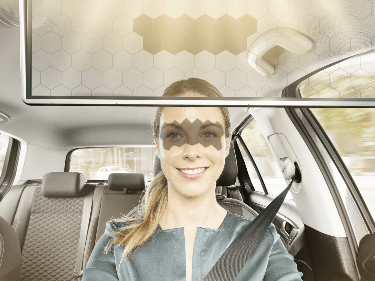 A woman driving in a car with a shadow on her eyes, which has been projected by a visor.
