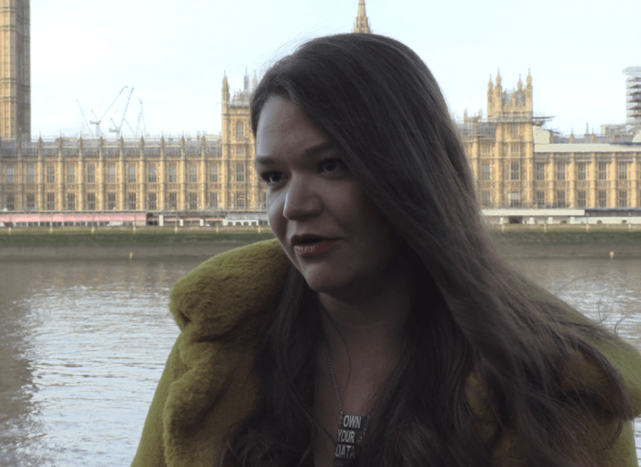 "A woman with long brown hair wearing a green fur coat and a silver necklace that says ""Own your data"", stands in front of the UK houses of parliament."
