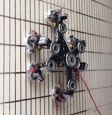 The large spider robot connected to a wire climbing a white tiled wall.