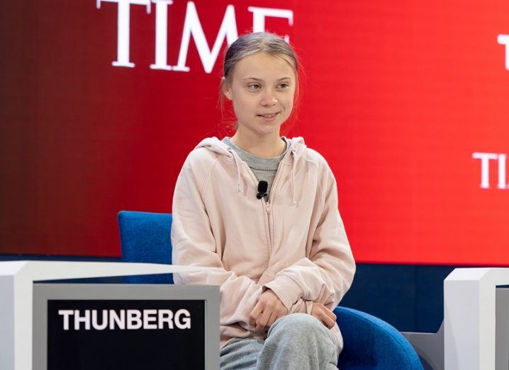 Greta Thunberg in a salmon coloured hoodie smiling, as part of a panel sitting against a red background.