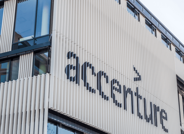 The facade of a building with white panels on it. It has the Accenture logo printed on it.