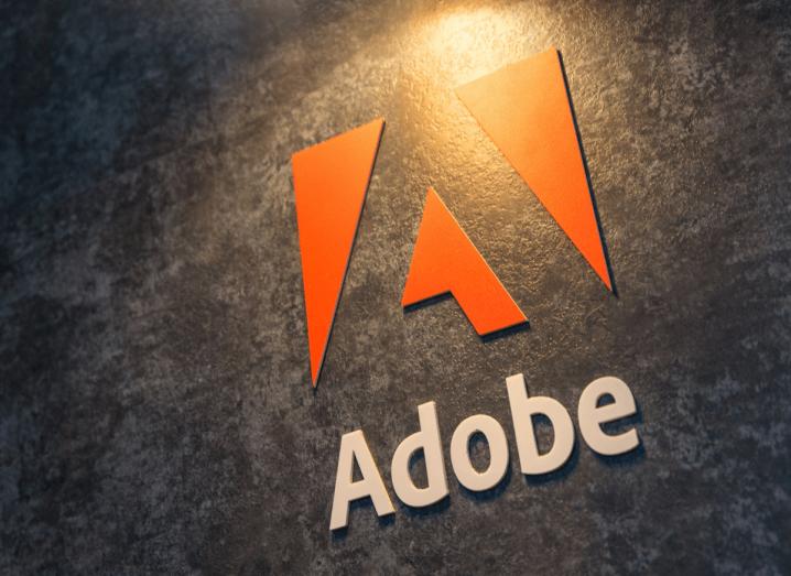 The Adobe logo on a grey wall.