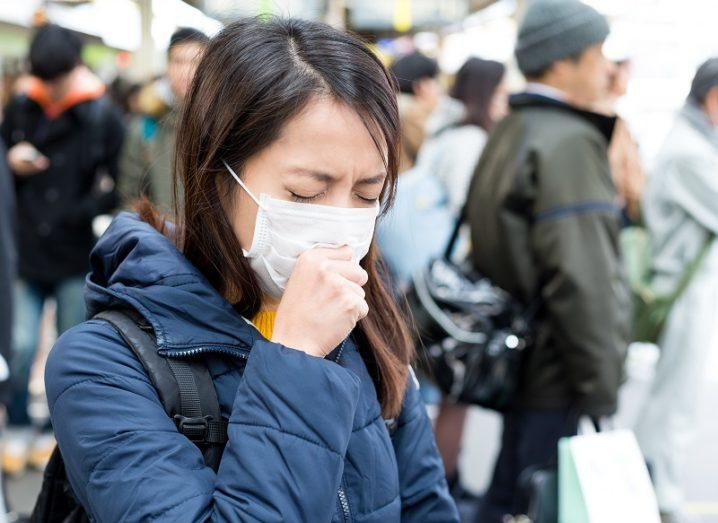 Woman wearing surgical mask on a busy street.