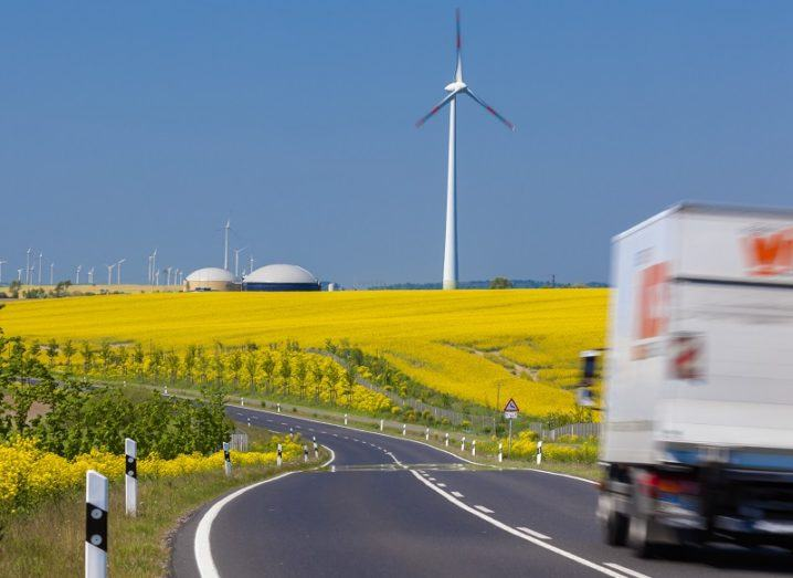 Blurred image of a passing truck on a empty road against a backdrop of yellow field and wind turbines.