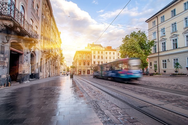 Blue tram blurred as it travels through an Oslo street with the sun shining in the background.