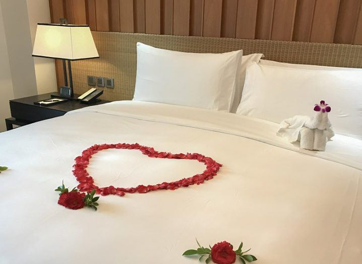White hotel bed with flower petals in the shape of a heart on it as well as flowers.
