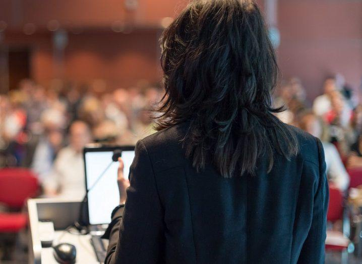 Rear view of a woman with black hair giving a presentation in a lecture hall.