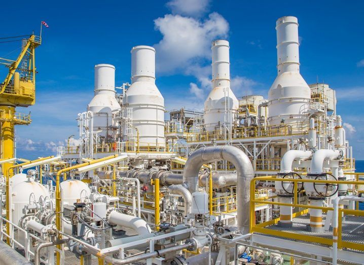 White pipes and chimney stacks at a natural gas processing plant.