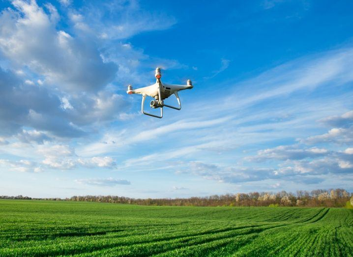 Flying white drone above a large green field against a blue sky background.
