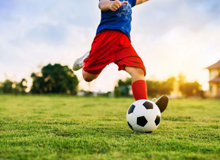A child wearing red shorts and a blue shirt kicking a football on a grass pitch against a sunny sky background.