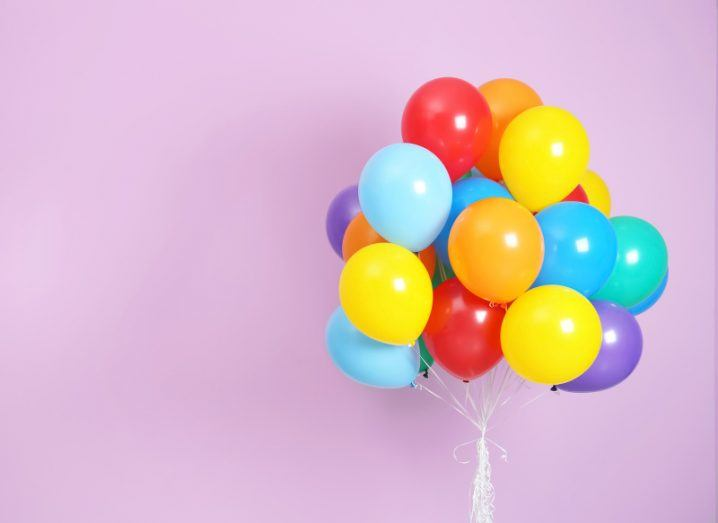 A colourful bunch of balloons gathered up against a dusky pink background.
