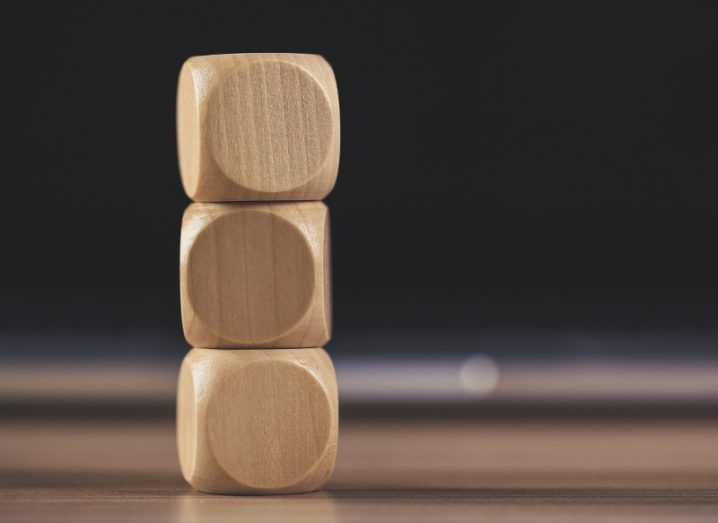 Three round-edged wooden cubes stacked one atop the other on a wooden table with a dark bokeh background.