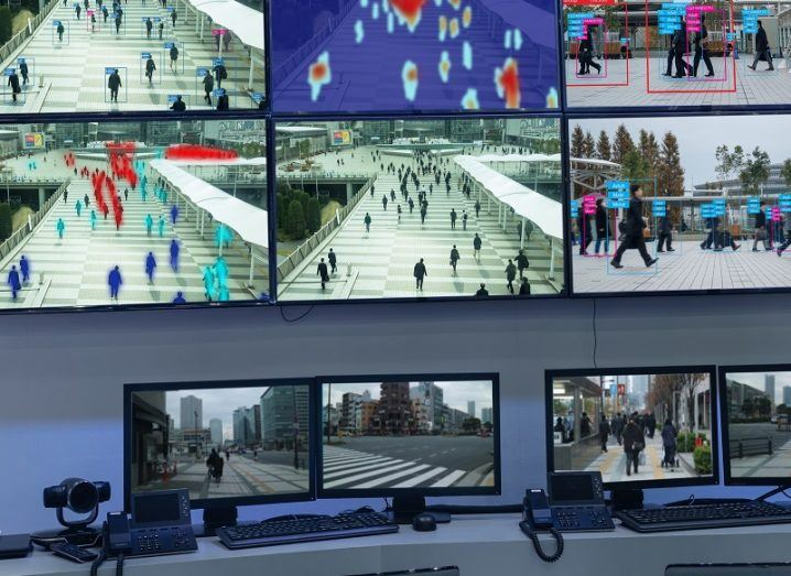 Control room with multiple screens showing people being publicly tracked with facial recognition.