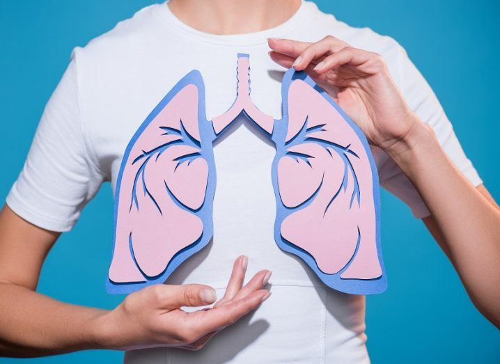 Person in a white T-shirt holding a 2D cut-out of lungs against a blue background.
