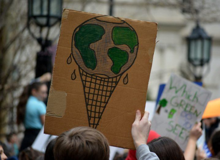 Close-up of a cardboard sign raised above a crowd at a climate protest, depicting Earth as a melting ice cream cone.