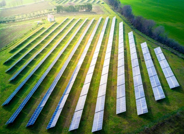 Aerial view of a solar farm receiving bright sunshine on a grassy field.