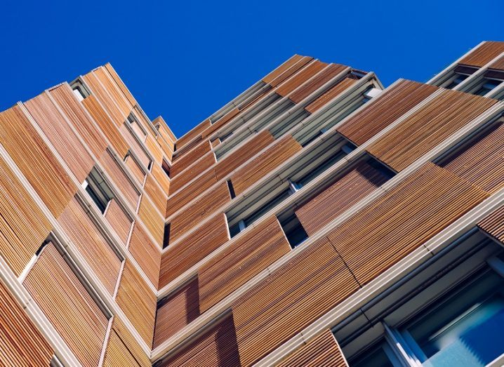 View looking up the outside of a tall, wooden building with a clear blue sky background.