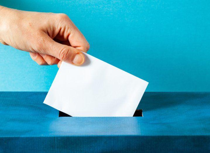 A hand placing a ballot into a blue box.