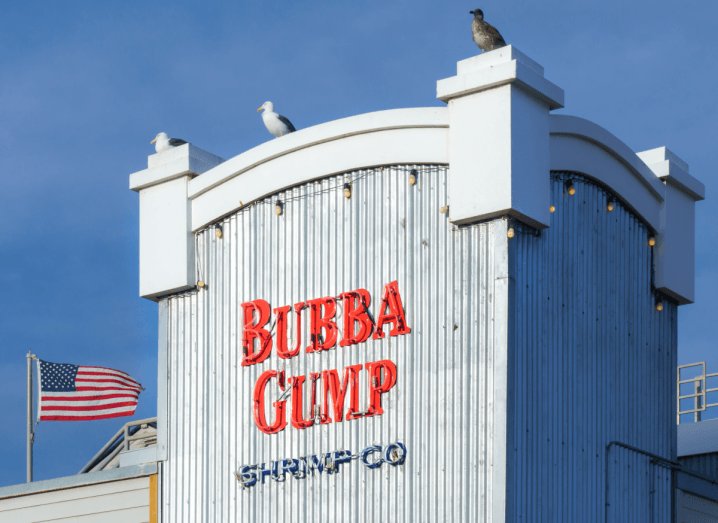 The deliberately shabby exterior of a white seafood restaurant with a red logo printed on the front. There is an American flag flying in the background beside the restaurant and two seagulls perched above the restaurant's logo.